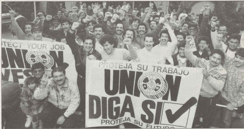 """A group of men raise their fists in celebration. The hold a sign in Spanish reading, """"Union, Yes!"""""""