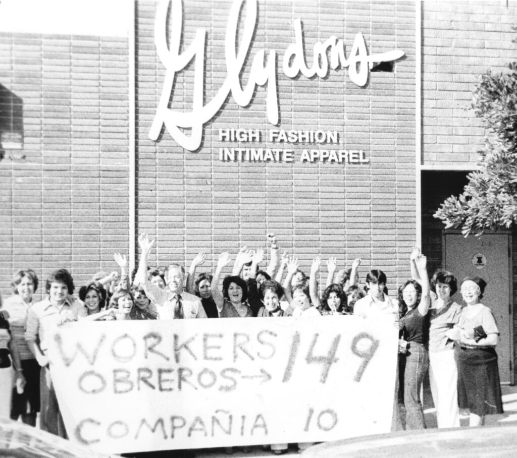 Workers celebrate a union victory outside of a garment factory in Los Angeles, 1980. They stand waving and smiling while holding a sign that indicates that 149 workers voted for the union and 10 against it.