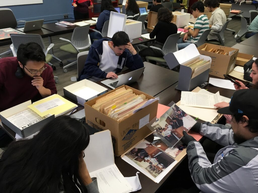 Students read from files drawn from archival boxes